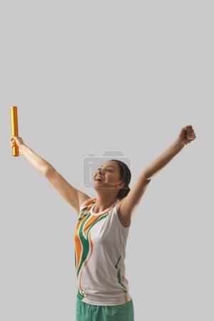 Female relay runner celebrating victory