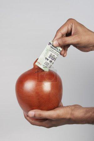 Photo pour Mettre de l'argent dans une tirelire - image libre de droit