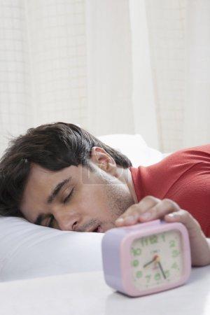 Man switching off his alarm clock