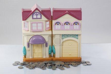 Photo pour Pièces de monnaie et de la maison de jouet - image libre de droit