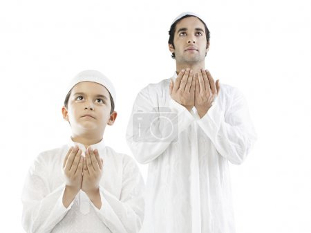 Muslim man and his son praying