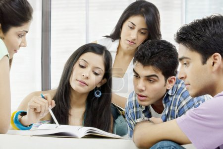 College students looking at a book