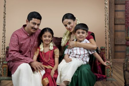 South Indian family sitting on a jhula