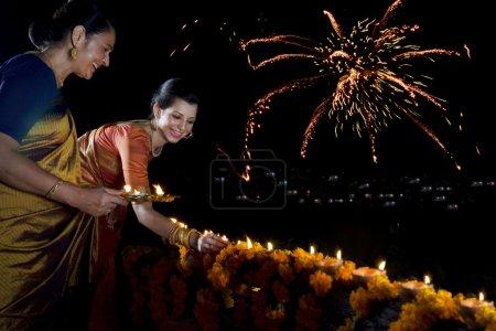 Mother and daughter lighting diyas