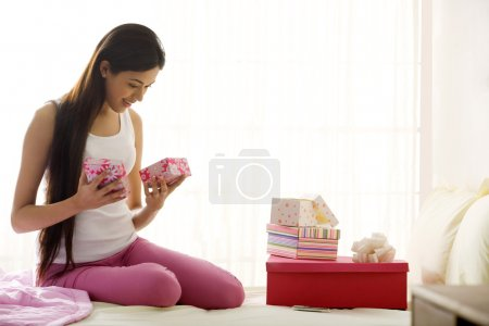 Girl looking at the contents of a gift box