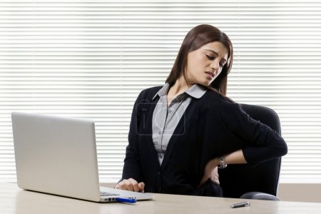 Businesswoman getting a backache in office