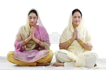 Mother and daughter praying