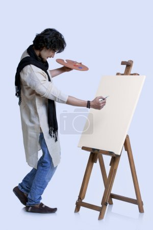 Young male artist painting