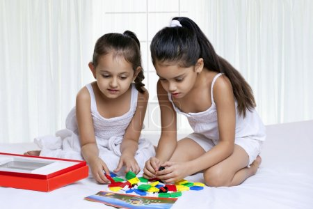 Children playing while sitting on bed