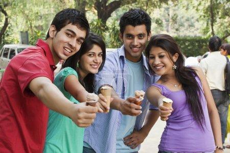 Happy friends holding ice cream