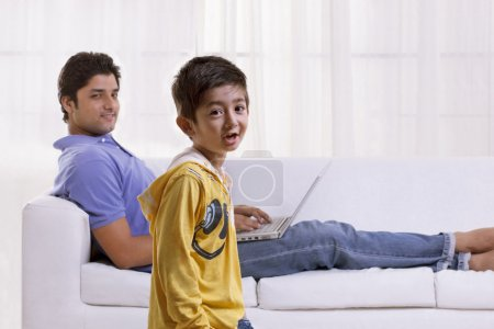 Boy holding felt tip pen with father using laptop