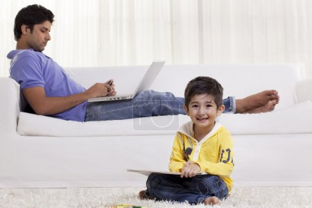 Boy holding felt tip pen with father using cell phone