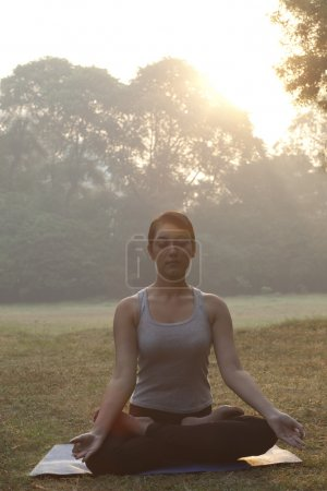 Woman meditating in lawn