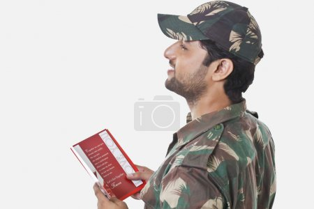 Happy soldier holding greeting card
