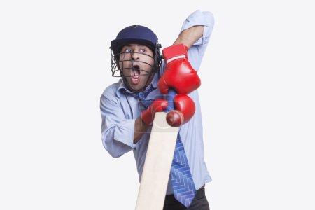 Businessman hitting ball