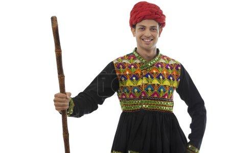 Male dandiya dancer with a stick