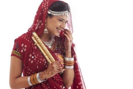 Portrait of a female dandiya dancer with sticks over white background