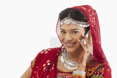 Dandiya dancer talking on a mobile phone