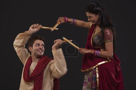 Portrait of couple dancing dandiya with sticks on black background