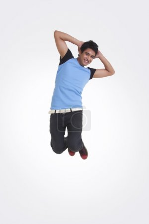 Full length portrait of young man with hands behind head jumping