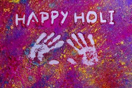 Photo pour Empreintes de main avec texte Happy Holi écrit sur rangoli - image libre de droit