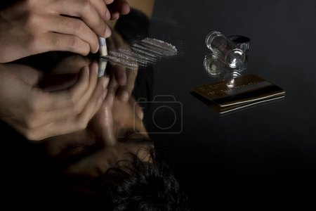 Close-up of man snorting drugs