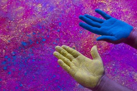 Photo pour Gros plan des mains montrant la peinture bleue et jaune puissance pendant le festival de Holi - image libre de droit