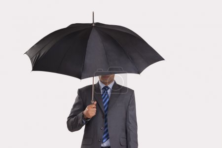 Young businessman hiding under umbrella