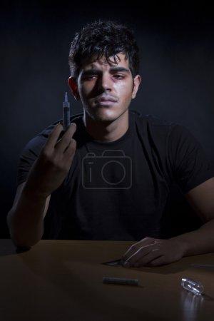 Male drug addict holding syringe
