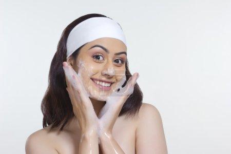 Smiling woman washing face