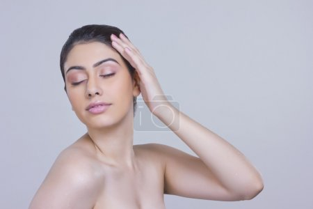 Young woman touching head