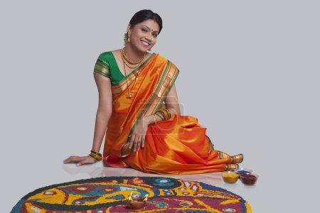 Maharashtrian woman making a rangoli