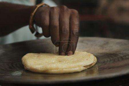 Photo pour Cropped image du mâle vendeur préparant kulcha - image libre de droit