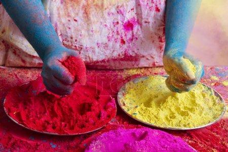 Photo pour Midsection de la personne tenant des peintures en poudre pendant le festival Holi - image libre de droit