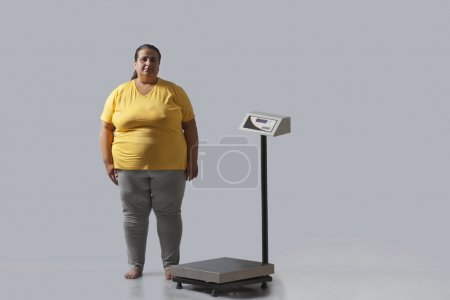 Portrait of obese woman with weighing scale