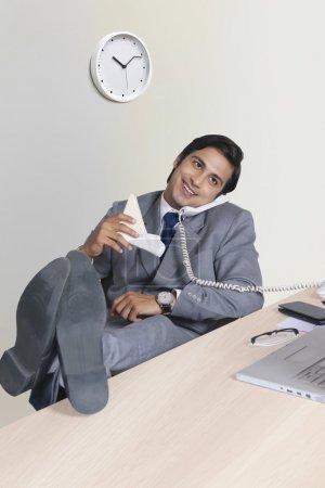 Relaxed businessman answering telephone