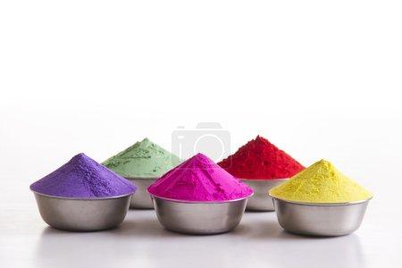 Photo pour Poudre Holi colorée en récipients sur fond blanc - image libre de droit