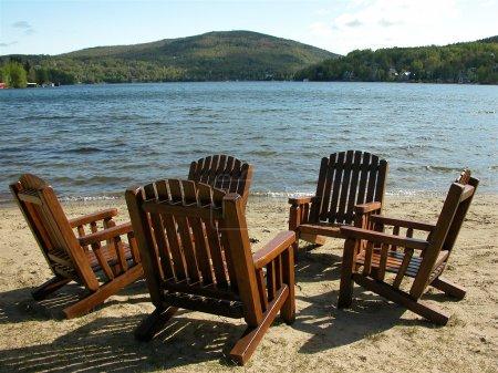 Photo pour Cinq chaises Adirondack sont placées en cercle sur la plage du lac Beauport . - image libre de droit