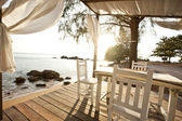 """Постер, картина, фотообои """"Белые кресла и столик на балконе с прекрасным видом на море"""""""