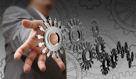 Photo for Businessman hand shows cogs as concept - Royalty Free Image