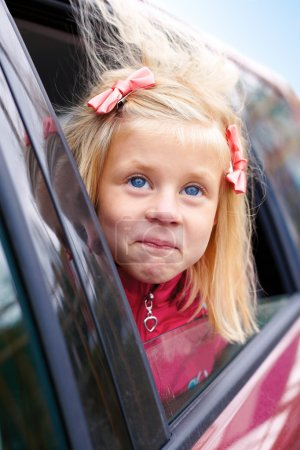 little girl surprise stares out of the car