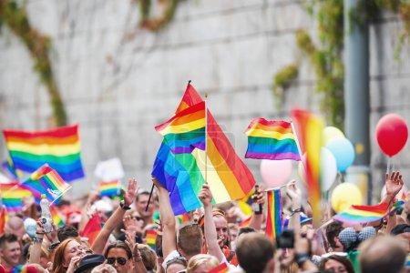 Happy crowd waving rainbow flags