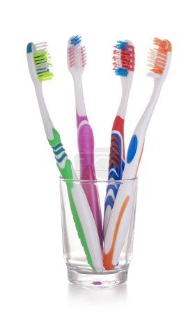 Photo pour Nouvelles brosses à dents colorées dans un verre isolé sur fond blanc - image libre de droit
