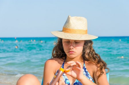 Photo for Applying sun block cream. beautiful tanned young teen with straw hat and glasses applying sun block cream on hand sitting on a beach - Royalty Free Image