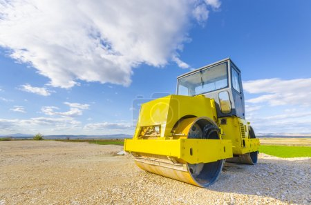 Yellow road-roller on repairing of the road