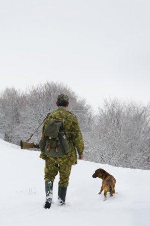 Photo pour Mâle chasseur en tenue de camouflage à pied sur le champ de neige avec fusil de chasse lors d'une chasse, chien le suit, temps brumeux - image libre de droit