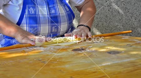 A Chef rolls dough to flatten it on wooden table