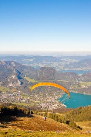 Photo pour Parapente au-dessus des montagnes et le lac wolfgangsee dans les Alpes autrichiennes - image libre de droit