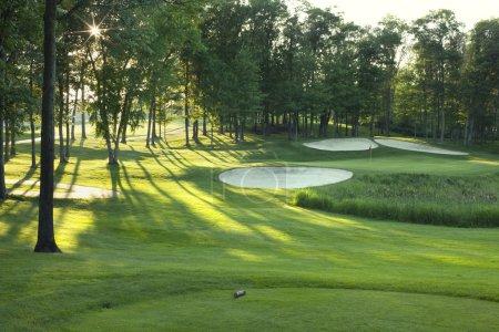 Foto de Golf tee caja y verde con árboles y trampas en la luz del sol por la tarde tarde - Imagen libre de derechos