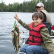 A young caucasian fisherman proudly holds up a str...